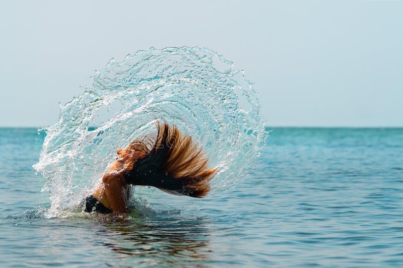 女孩在水中的翻转头发 库存照片