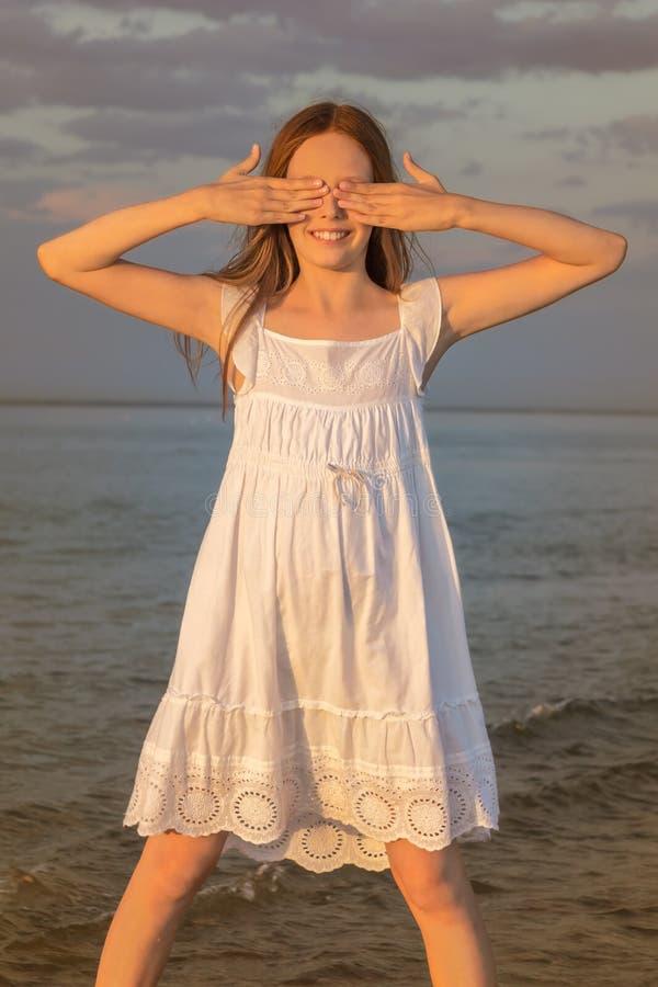 女孩在水中站立,注视闭合的手 图库摄影