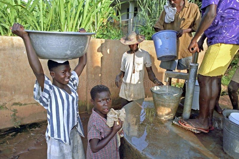 女孩在水泵的取指令水 免版税库存照片