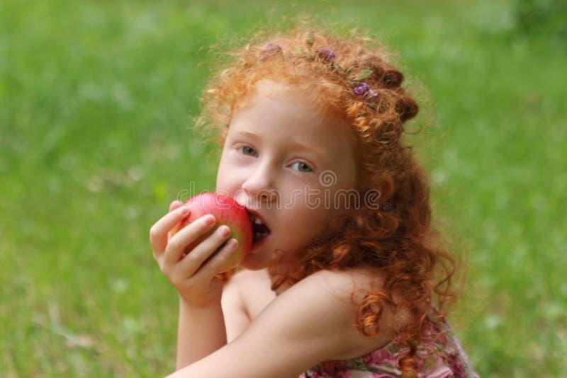 女孩在绿色夏天公园,关闭吃光在草坪的苹果, s 免版税库存图片