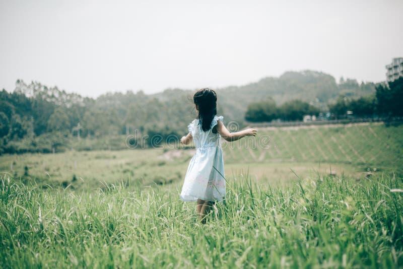 女孩在绿色庭院里 免版税库存照片
