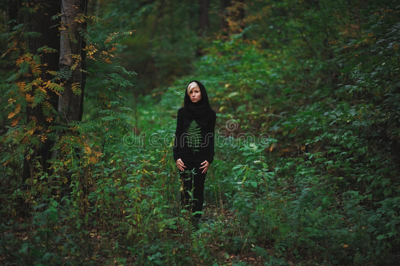 女孩在绿色森林中站立 免版税库存图片