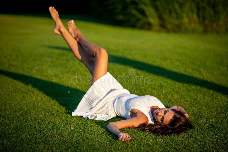 女孩在绿草放松 库存图片