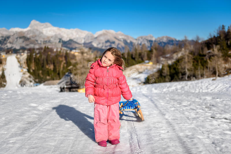女孩在滑雪胜地佩带的冬天拉扯雪爬犁穿衣 库存图片