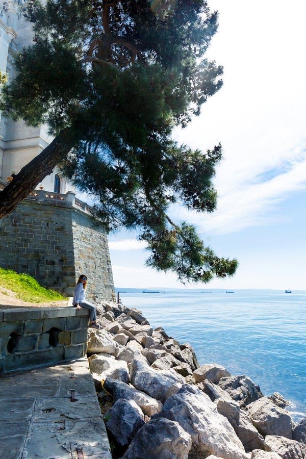 女孩在Miramare城堡附近坐在意大利 免版税库存照片