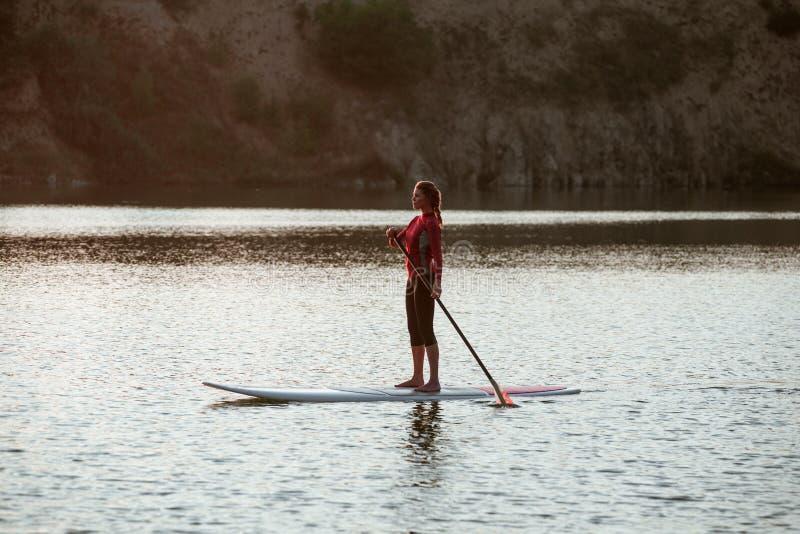 女孩在sunset11的桨搭乘剪影  库存图片