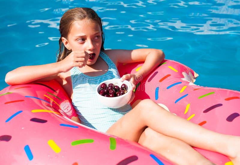 女孩坐一个五颜六色的可膨胀的多福饼用樱桃 免版税图库摄影
