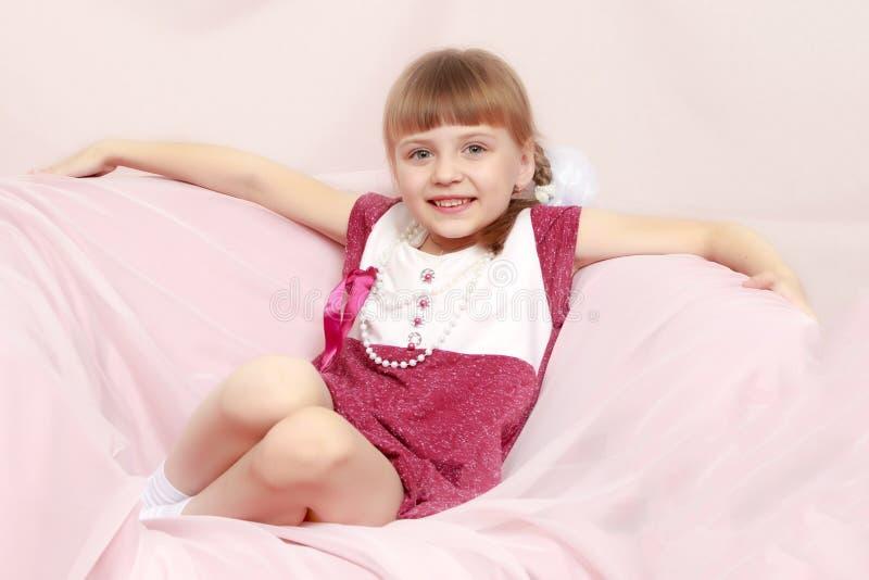 女孩坐一个桃红色沙发 免版税库存照片