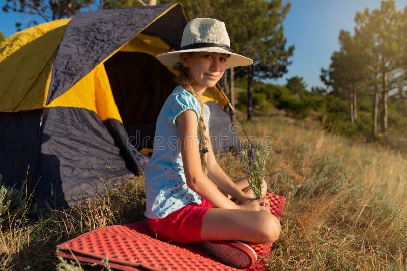 女孩坐一个红色地毯在帐篷附近,拿着野花花束,野营 免版税库存照片