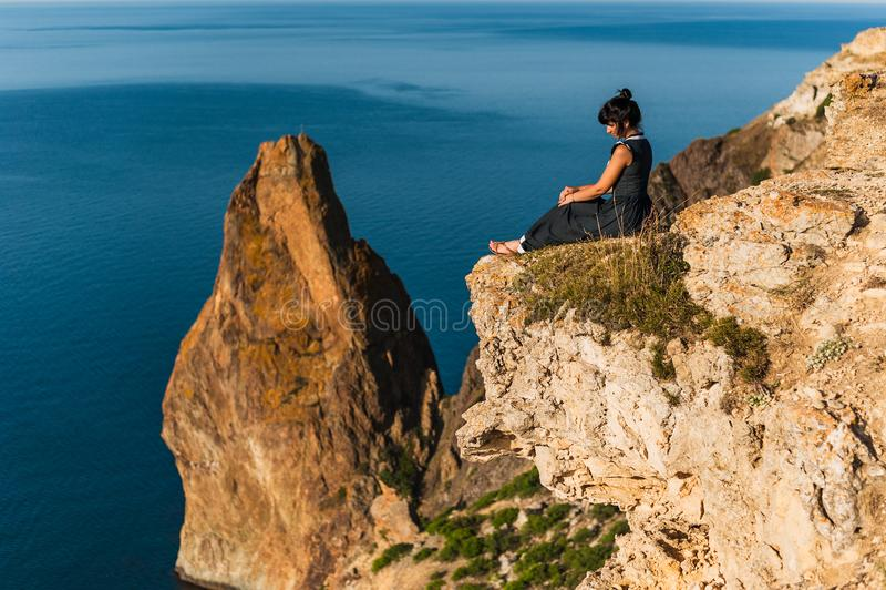 女孩坐一个高岩石并且看海 免版税库存照片