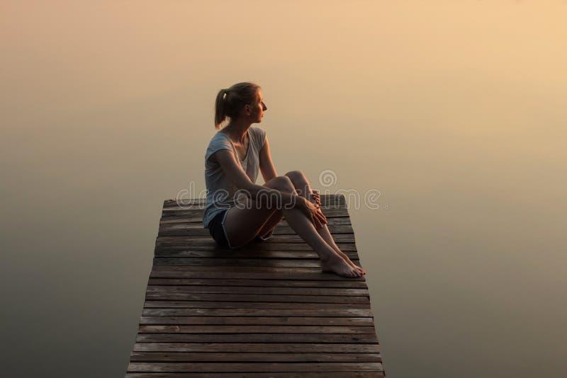 女孩坐一只木码头或跳船在湖在日落 免版税库存照片