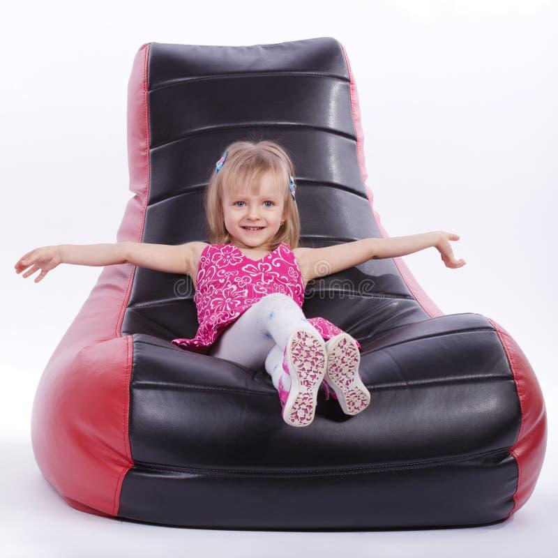 女孩坐一把软的现代椅子 库存照片