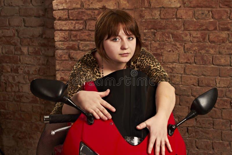 女孩坐一辆红色摩托车 库存照片
