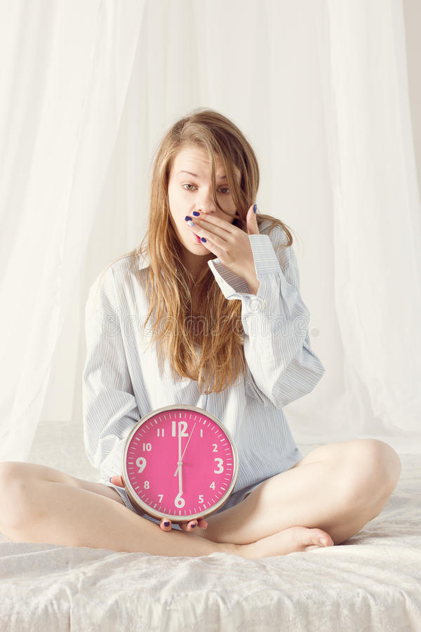 女孩坐与大桃红色时钟的床 6 a M 库存照片