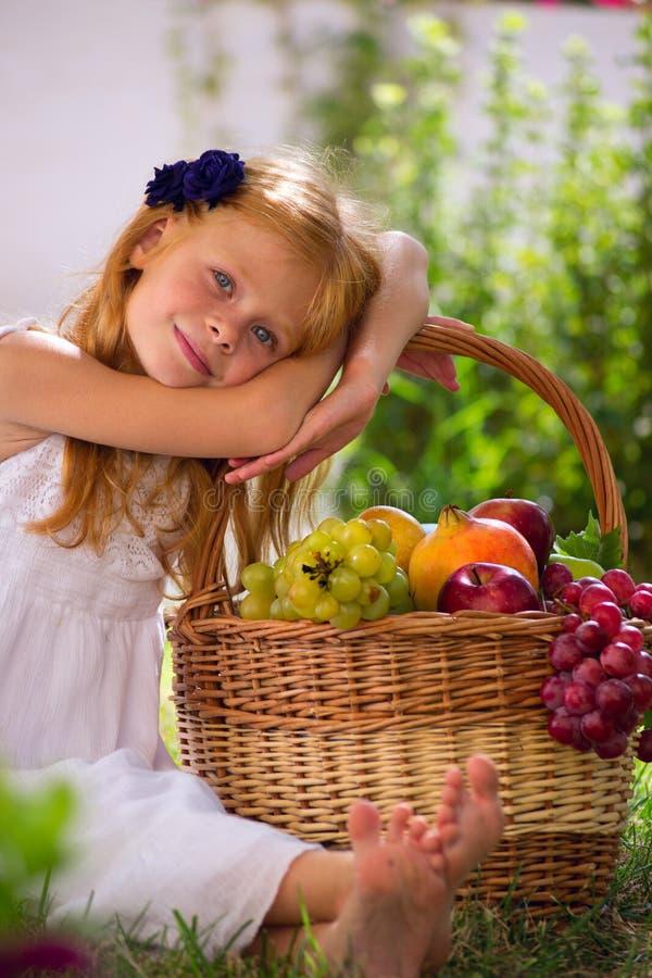 女孩坐与果子篮子的草  免版税库存图片