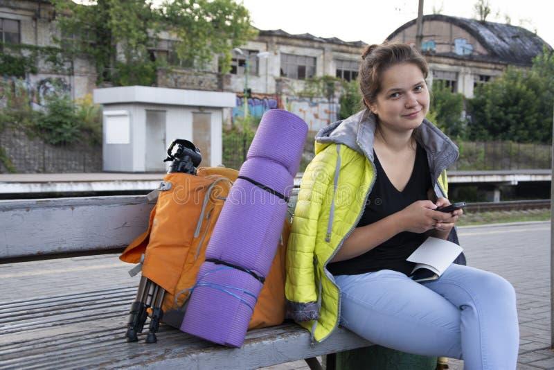 女孩坐与背包和野营的设备 库存照片