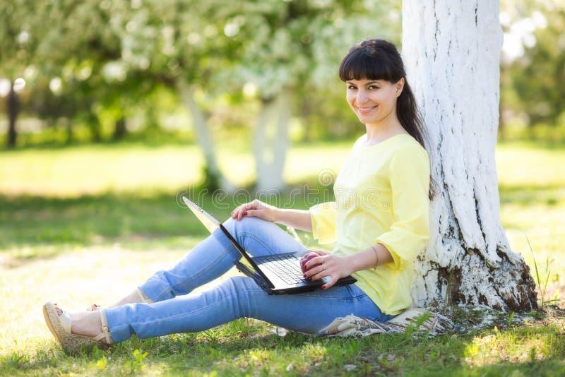 女孩坐与膝上型计算机在树附近 库存照片