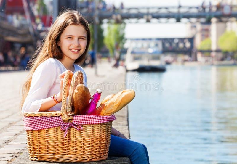 女孩坐与野餐篮子的堤防 免版税图库摄影