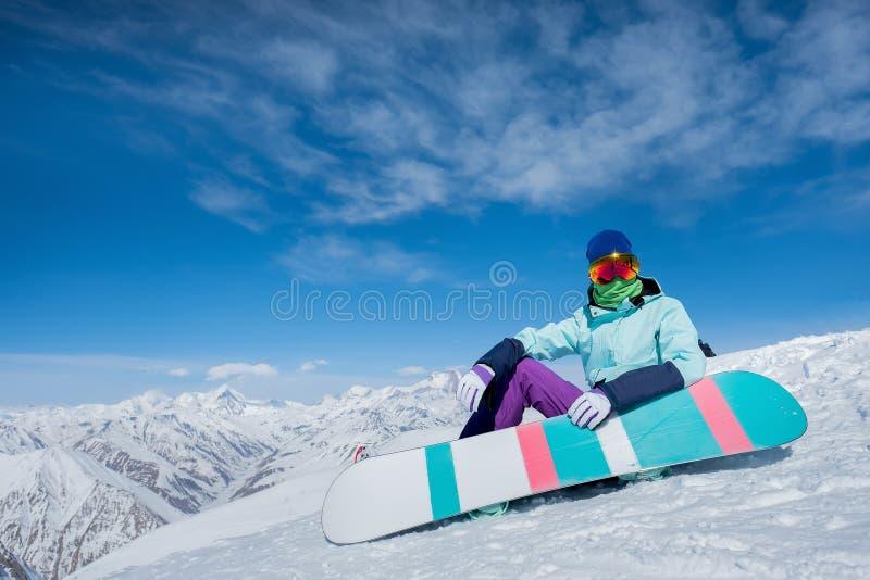 女孩坐与雪板板的雪 冬天 的treadled 库存照片
