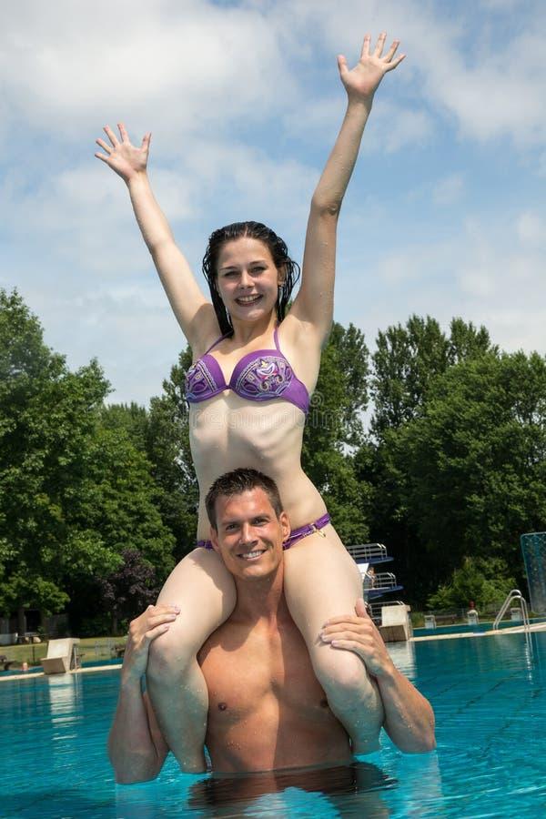 女孩坐人的肩膀在游泳池 库存照片