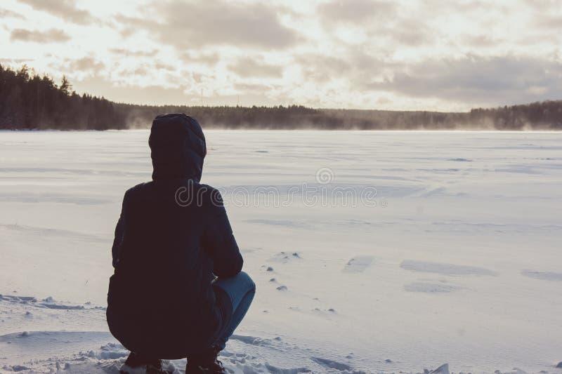女孩坐冬天湖的岸 库存图片