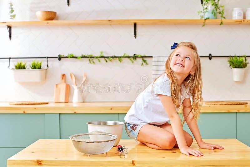 女孩坐厨房木桌 库存照片