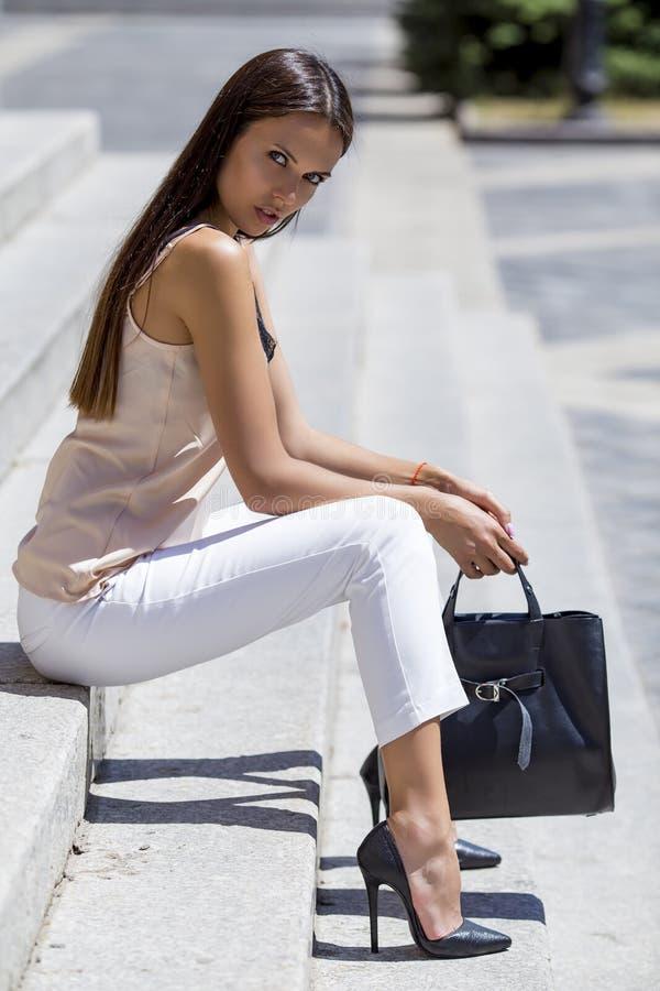 女孩坐在别致的鞋子的台阶有一个时髦的黑袋子的 库存图片