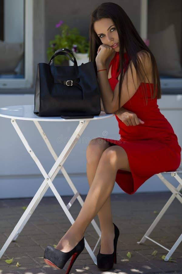女孩坐在别致的鞋子的椅子有一个时髦的黑袋子的 免版税图库摄影