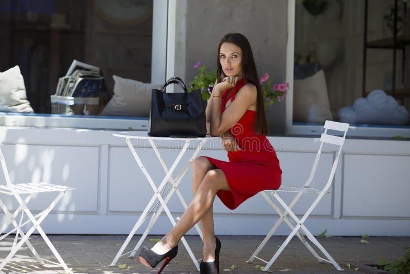 女孩坐在别致的鞋子的椅子有一件时髦的黑袋子和红色礼服的 免版税库存照片