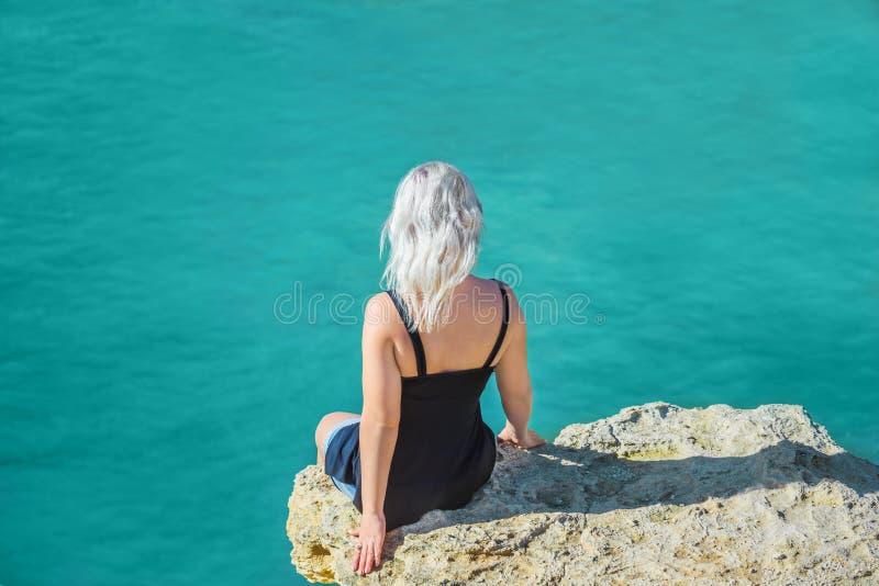 女孩坐在海洋上的峭壁 免版税库存照片