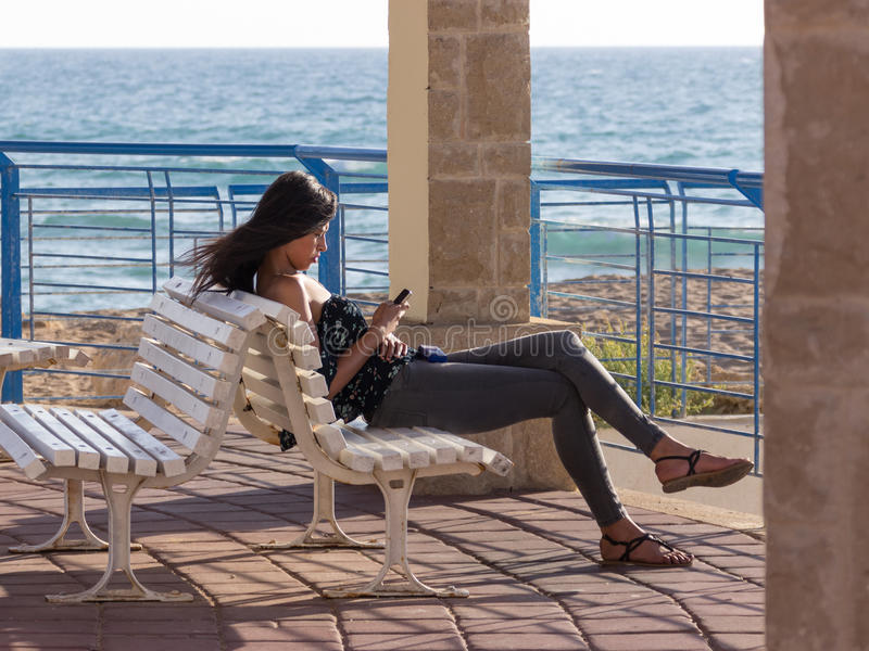 女孩坐在海滩的日落,并且写了消息  免版税库存图片