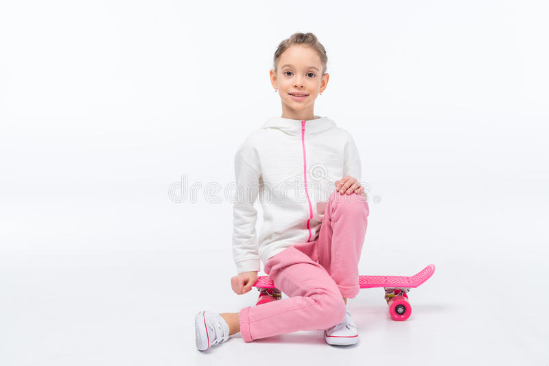 女孩坐在白色的滑板 免版税库存照片
