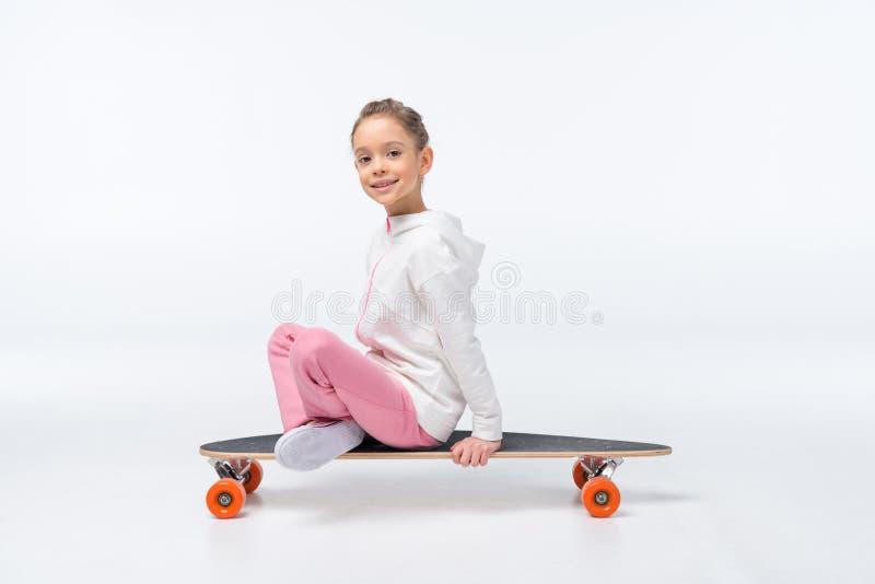 女孩坐在白色的滑板 免版税库存图片