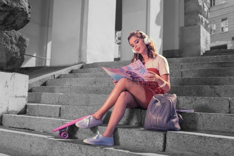 女孩坐在读时尚和听的台阶到音乐之外 库存图片