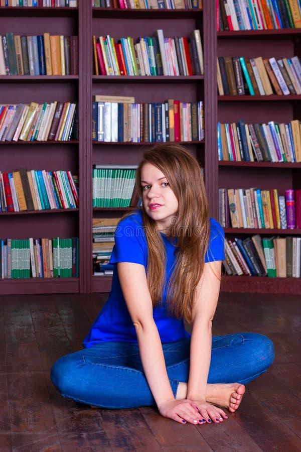女孩坐地板在图书馆里 免版税图库摄影