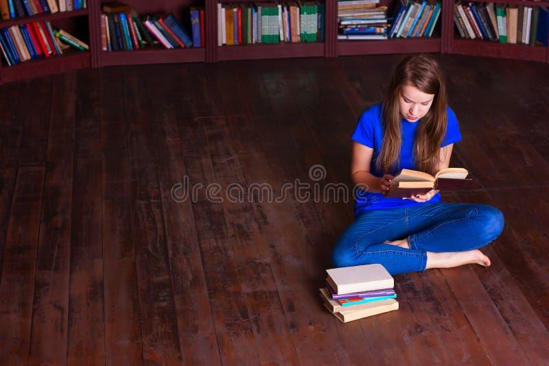 女孩坐地板在图书馆里 库存图片