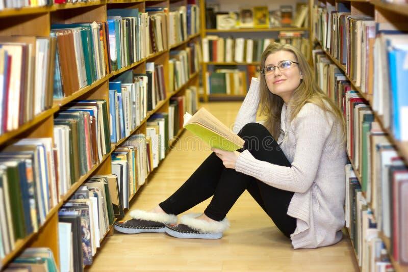 女孩坐地板在老图书馆里 库存图片