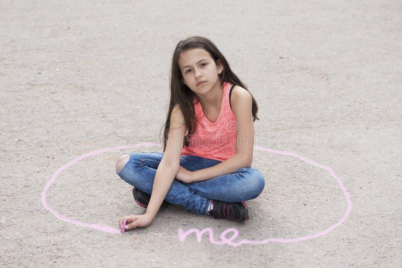 女孩坐地面和画的个人空间 免版税库存图片