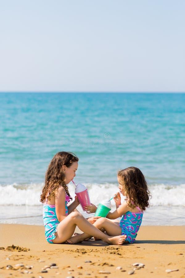 女孩坐坐在彼此对面和从色的美好的鸡尾酒杯家庭度假概念喝 免版税图库摄影