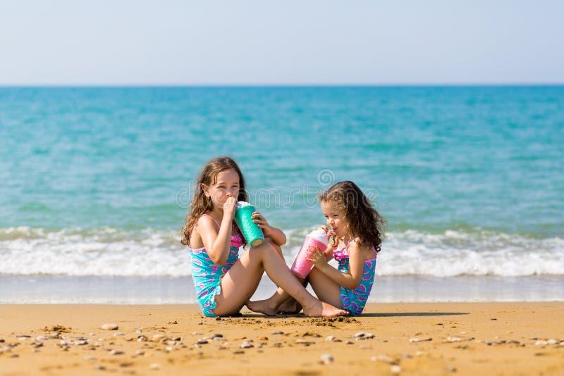 女孩坐坐在彼此对面和从色的美好的鸡尾酒杯家庭度假概念喝 库存图片