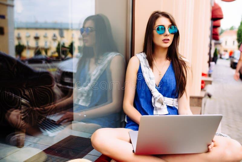 女孩坐室外用在太阳镜的咖啡 库存图片