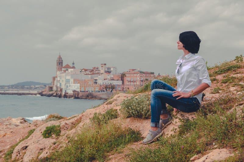 女孩坐小山有海和城市背景 图库摄影