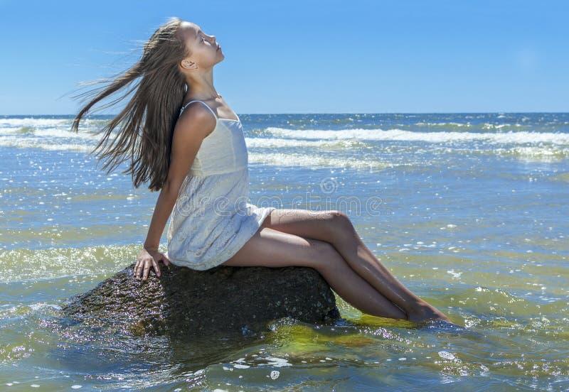 女孩坐岩石由波罗的海 库存图片