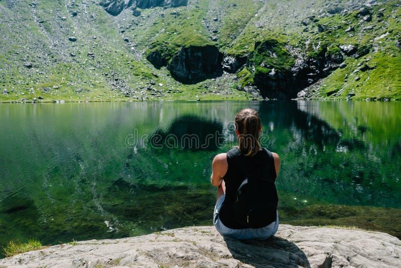 女孩坐岩石,看反射在湖的山的一个壮观的看法 免版税库存照片