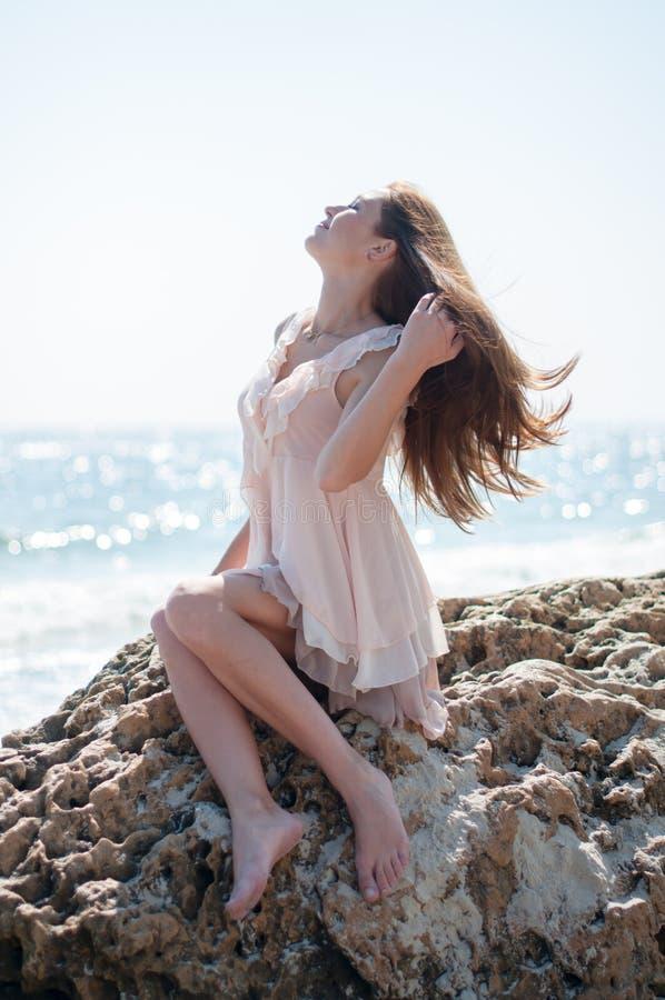女孩坐岩石 图库摄影