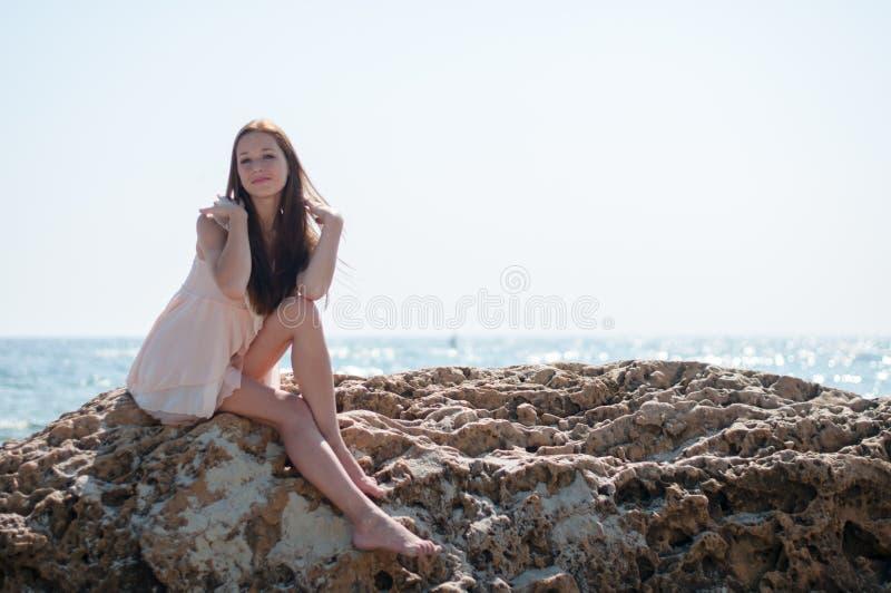 女孩坐岩石 免版税图库摄影