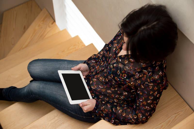 女孩坐并且看片剂的屏幕,读新闻 r 女商人在家计算机的 库存图片