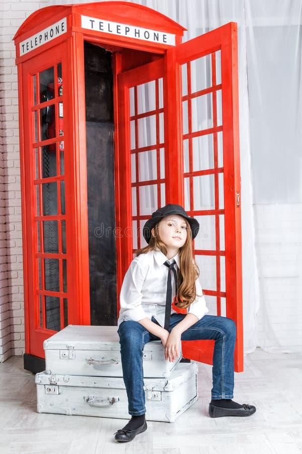 女孩坐手提箱在电话亭附近 免版税图库摄影