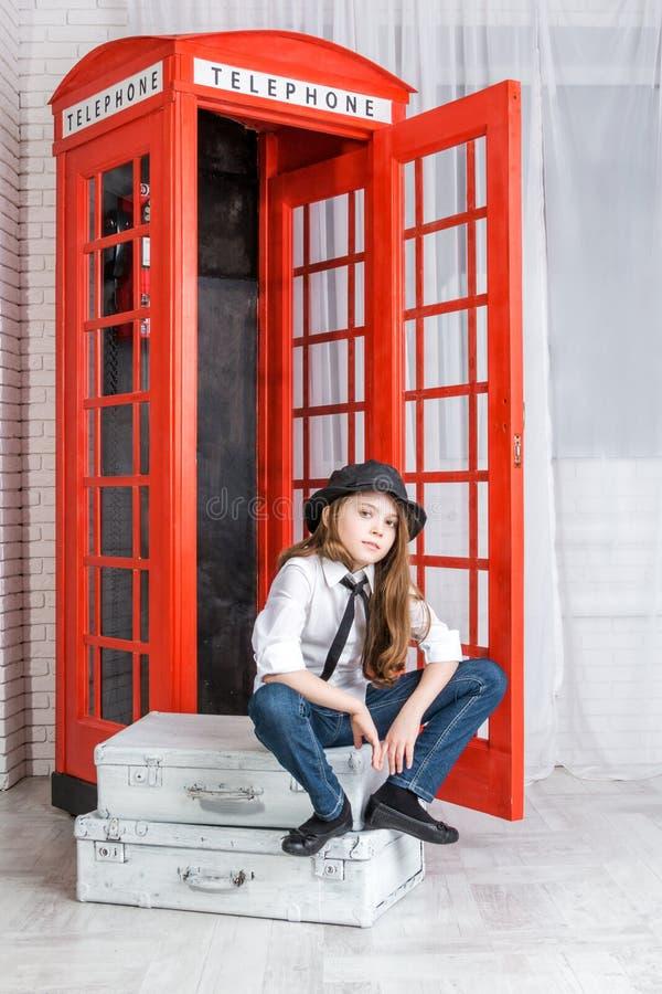 女孩坐手提箱在电话亭附近 图库摄影