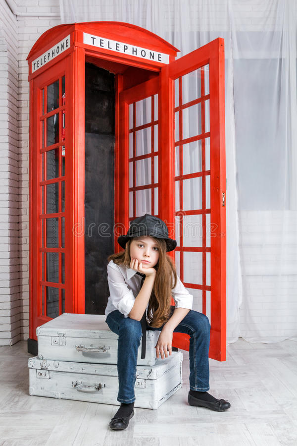 女孩坐手提箱在电话亭附近 库存图片